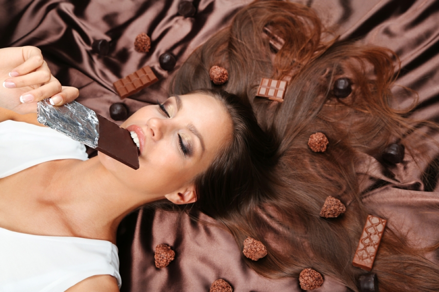 hypnotherapy for food addiction in Your Town - woman eating and surrounded by chocolate